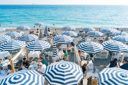 Nice, OCT 20: The beautiful Nice beach with many visitor hiding in beach umbrellas on OCT 20, 2018 at Nice, France Editorial
