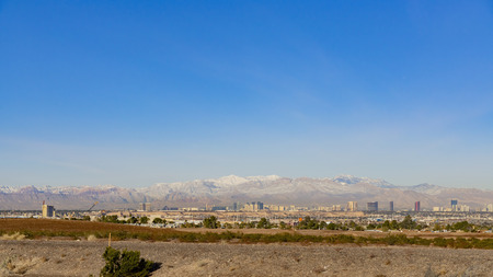 Morning view of the famous Strip of Las Vegas with snowy mountain behind