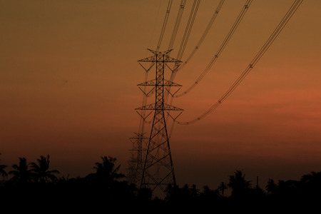 silhouette of high voltage towers at sunset