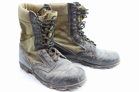 Old army boots isolated on white .