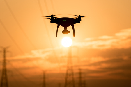 Silhouette of drone flying  at sunset