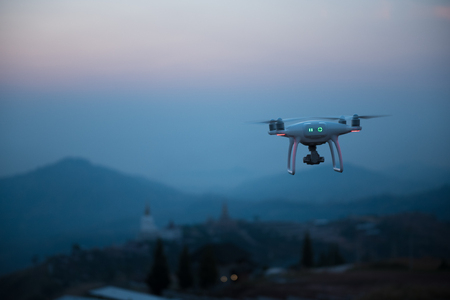 Drone flying on a mountain view at beautiful twilight sky. Vehicle at sundown and copy space. Standard-Bild