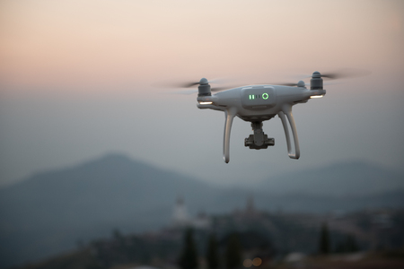 Drone flying on a mountain view at beautiful twilight sky. Vehicle at sundown and copy space. Stock Photo