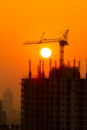 Tower crane  silhouette on construction site at sunset in Thailand