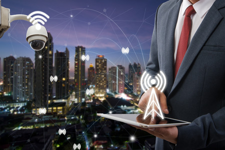 Double exposure of a businessman and a city using a tablet, and cctv Security cityascape and network concept