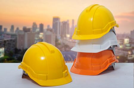 Il casco di sicurezza impilato sullo sfondo è un quartiere degli affari.