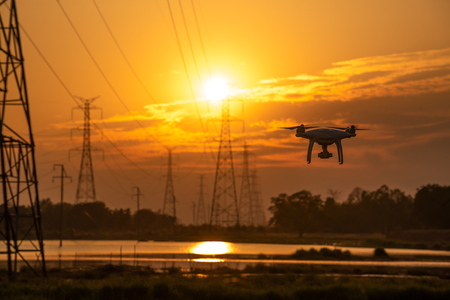 Drone surveying High voltage towers the sunset background