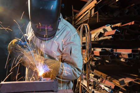 A welder is welding steel in an industrial factory. The welder wears protective clothing to work in the workplace. Фото со стока