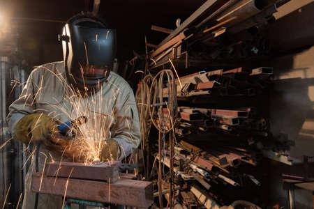 A welder is welding steel in an industrial factory. The welder wears protective clothing to work in the workplace. Banco de Imagens
