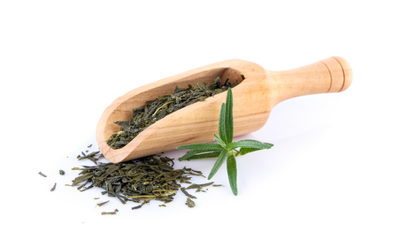 dry geen tea in scoop on white background Stock Photo