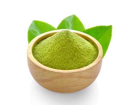 powder matcha green tea in wood spoon on white background