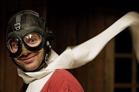 pilotos aviadores: Smiling hombre con casco, gafas de vuelo y agitando bufanda
