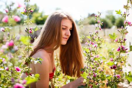 healthy llifestyle: young beautiful woman blond at nature, surrounding by wild mallows