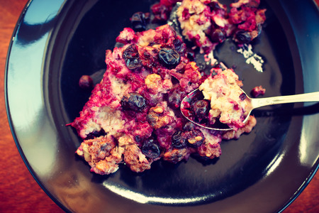 blackcurrant: oatmeal, blackcurrant and walnut casserole on plate with spoon, toned