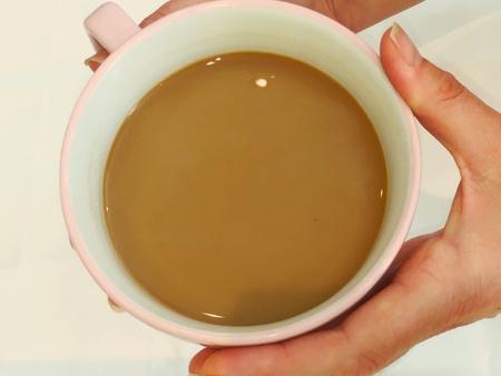 cradling: Hand cradling cup of coffee