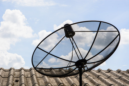 communications tools: satellite dish on the roof with blue sky Stock Photo