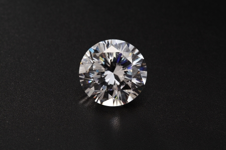 cut diamonds on shiny black surface close up