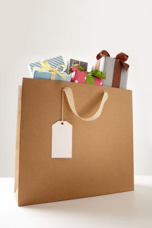 Shopping Bag of presents on white table.  brown Shopping bag. Banco de Imagens