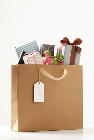 화이트 테이블에 선물 쇼핑 가방. 갈색 쇼핑 가방입니다. 스톡 콘텐츠