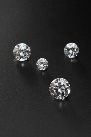 cut diamonds on shiny black surface close up. more diamonds out of focus in background  Banco de Imagens
