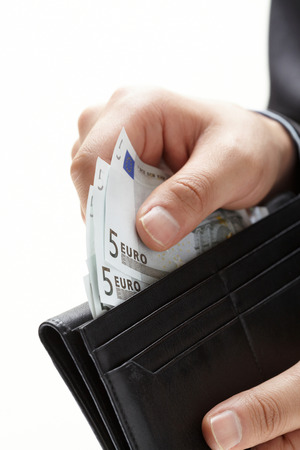 A hand holding an money with black wallet
