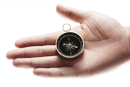 orienting: compass in hand isolated on white background