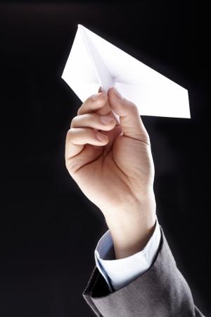 Handmade white origami paper plane isolated on black background photo