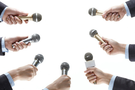 press conference: hand holding out a microphone isolated on white background