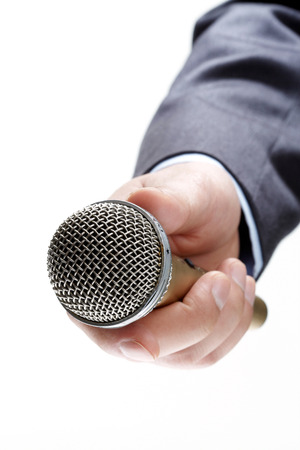 public address: hand holding out a microphone isolated on white background