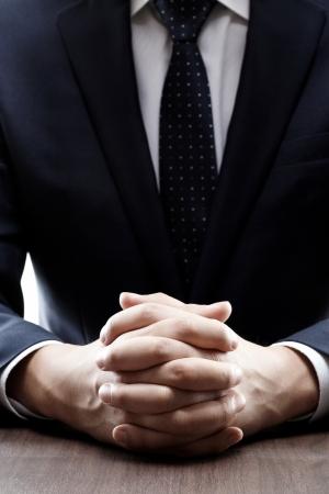 entrevista de trabajo: primer plano de un hombre en un traje con las manos cruzadas delante de él