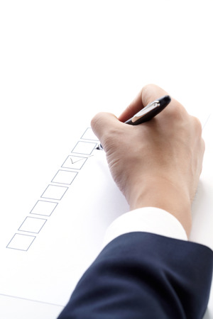 filling of questionnaire a person by a pen on white background