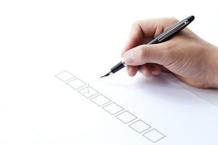 questionnaire: filling of questionnaire a person by a pen on white background