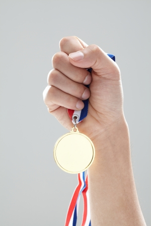 Golden medal in man hand Standard-Bild