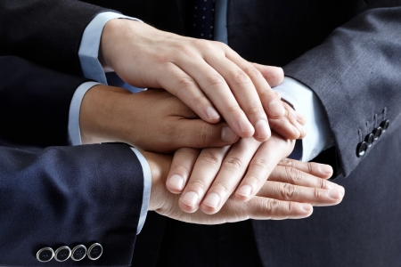 joining hands: business people hands on top of each other Stock Photo
