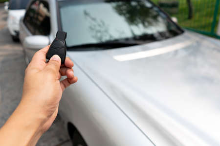 Close up hand press the remote control to unlock or lock car at garage or parking lot. Technology of automotive security system to anti theif by hack remote radio frequency. Blur background for copy space.