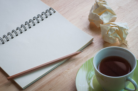 waste paper: Working with blank notebook on wooden desk background with coffee cup and waste paper Stock Photo