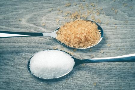 Weißzucker und brauner Zucker und ein Löffel auf einem Bretterboden