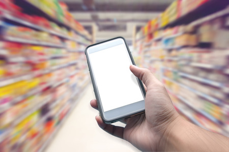 zooming: Mobile phones while shopping in a supermarket. Zooming back