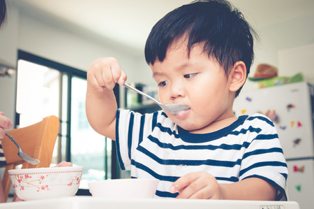 asian toddler: Asian toddler boy eating on high chair Stock Photo