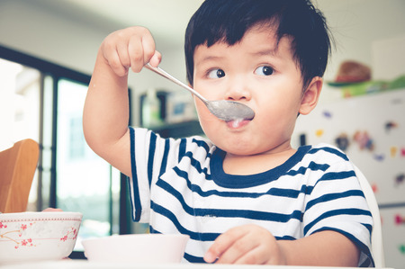 Asian toddler boy eating on high chair Stock fotó