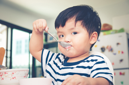 high chair: Asian toddler boy eating on high chair Stock Photo