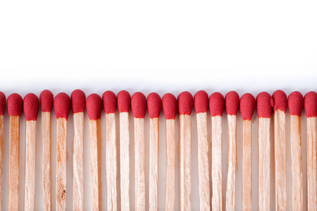igniting: Close-up of red matches on white background.