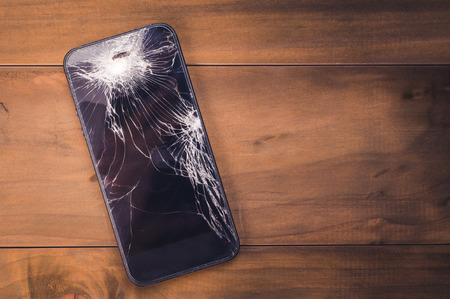 Smartphone mobile with a broken screen. Background wood