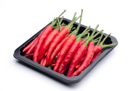 dietetics: Heap of red hot chili pepper in black container on white background.