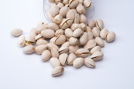 Roasted and salted pistachios in shell on white background. Stock Photo