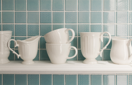 Clean cups on wooden shelf