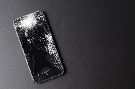 Smartphone with broken screen on dark background