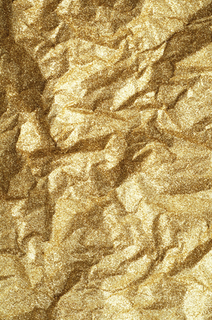 Gold wrinkled paper texture abstract background.