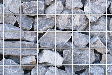 gabion mesh: Steel mesh of gabion wall.Grey stones in gabion.