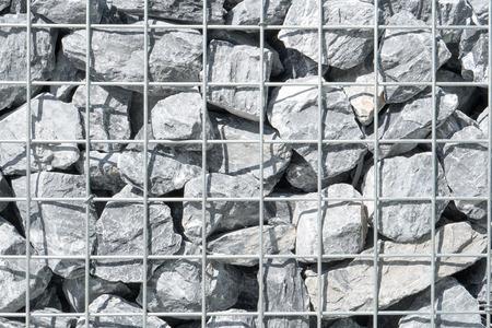 Steel mesh of gabion wall.Grey stones in gabion.